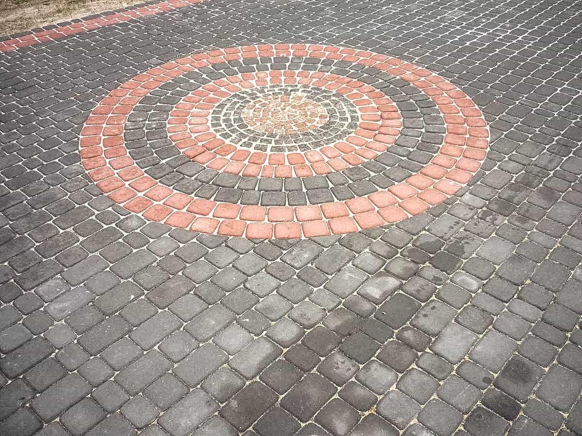 Okrągły wzór ułożenia kostki w szarości i czerwieni.